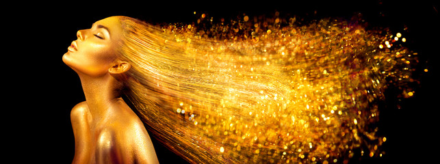 Fashion model woman in golden bright sparkles. Girl with golden skin and hair portrait closeup....