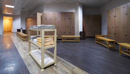 Clean towels shelf in a locker room with wooden benches in luxury fitness gym