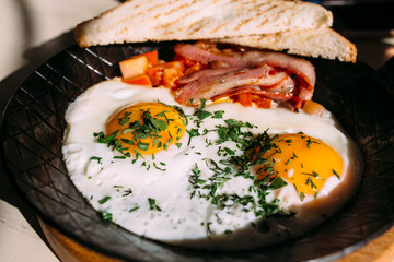 Fried eggs, bacon, tomatoes at toast. Classic breakfast food in iron pan