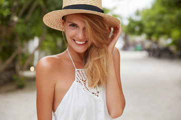Photo of pleased adorable female model wears white dress and summer straw hat, has walk outdoor, enjoys hot shiny weather, has tanned skin, perfect teeth, smiles at camera. Beauty and rest concept