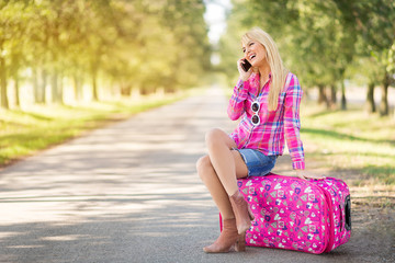 Beautiful cheerful young blonde women sitting on suitcase and talking on smartphone along the road. Happy female traveler going on vacation