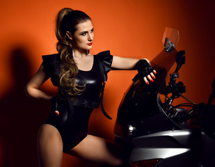 Young sexy fashion woman sitting posing on motorcycle in studio