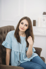 beautiful young stylish woman is sitting on the sofa hands