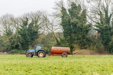Day view tractor fertilizer sprays on British field