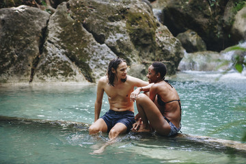 Couple sitting together in a natural pond with clear water