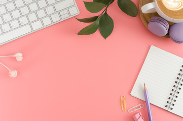 Styled stock photography pink office desk table with blank notebook, keyboard, macaroon, supplies and coffee cup. Top view with copy space. Flat lay.