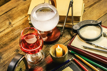 pencils, notebook, books, compasses, a glass of wine and an ancient barometer on a wooden table. workspace in vintage style.