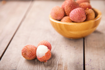 Fruits lychee in a bowl on a wooden background. Selective focus. Copy space.