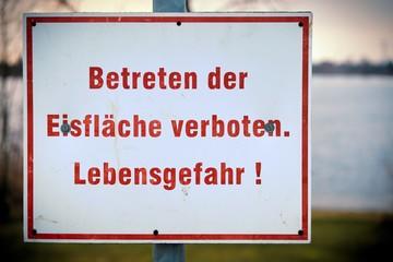 Schild mit der Aufschrift Betreten der Eisfläche verboten an einem See im Winter