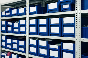 Blue plastic boxes placed in shelves.