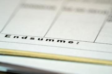 Aktenordner auf einem Schreibtisch im Büro mit dem Schriftzug Endsumme