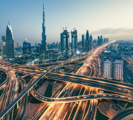 Aerial view over big highway interchange and skyscrapers in Dubai, UAE, at sunset. Scenic cityscape. Toned travel and architectural background.
