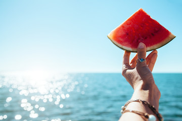 Watermelon slice in woman hand over sea