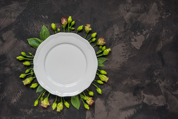Empty plate framed flowers, top view. Plate over lisianthus on a dark background