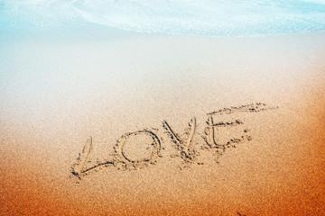 love inscription on the sand near the sea