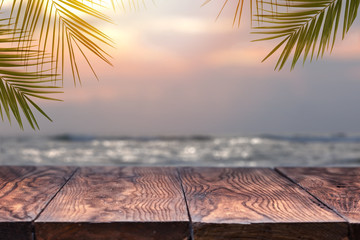 Empty wooden table and palm leafs on a background of beach blurred.