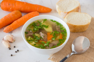 Soup with meat, potatoes and carrot. Beef soup in a white bowl