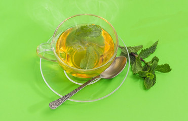 Tea with mint in glass cup on a green background