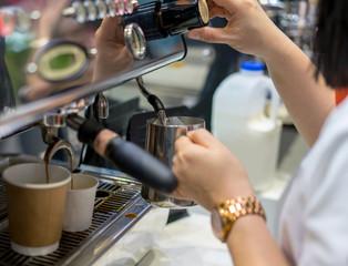 Barista hand adjusting level of steam pressure for milk frothing for espresso shot