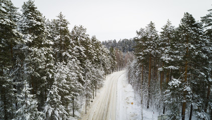 Aerial view of a winter road. Winter landscape countryside. Aerial photography of snow forest. Captured from above with a drone. Aerial photography