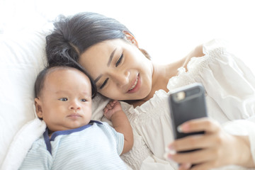 Mother holding smartphone for taking photo with her baby. Technology concept.