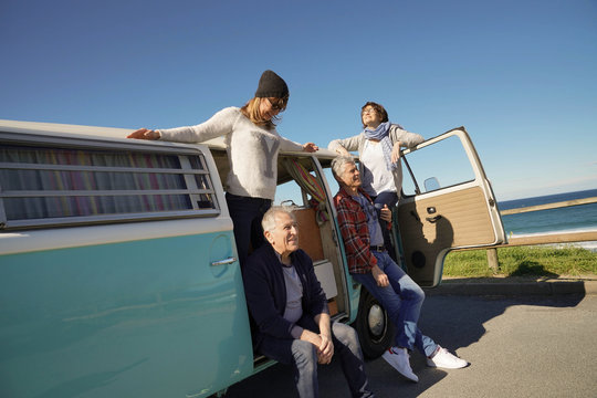 Senior people on a road trip with camper van enjoying stop by the sea