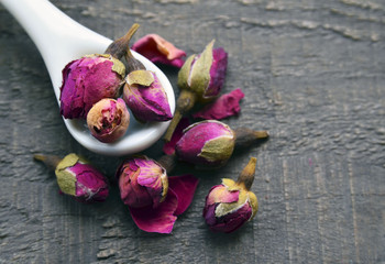 Dry rose buds flowers in a white spoon on old wooden table.Asian ingredient for aromatherapy herbal tea.Selective focus.