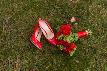 Fotobehang Female fashion red wedding shoes with bride's bouquet of red roses and green berries on green grass background.