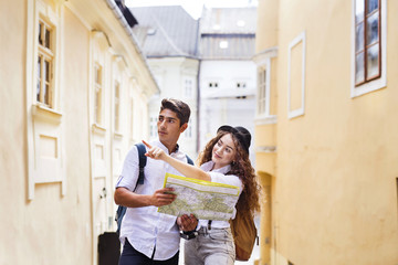 Two young tourists with map and camera in the old town.