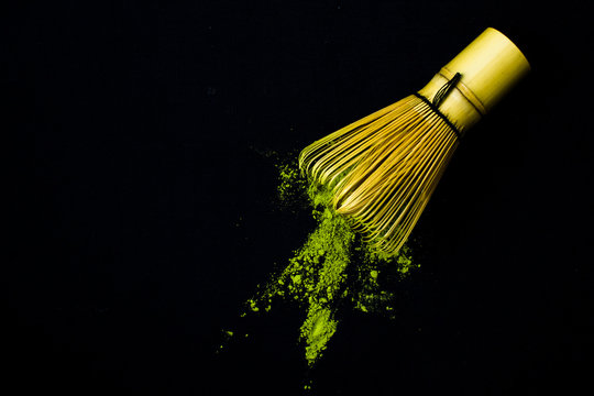 Close up bamboo whisk and matcha green tea powder on black background.