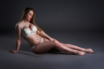 Plus size sexy model in white underwear, fat woman sitting on gray background, overweight female body
