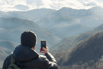 Hiker takes photo of beautiful mountains