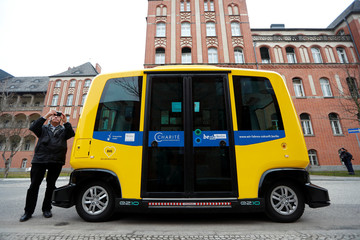 A man takes a picture next to a self-driving shuttle bus, operated by the university hospital Charite and public transport company BVG, during a presentation to the media at the Charite Campus in Berlin