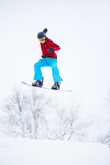 Image of sportive male snowboarder jumping on snowy hill