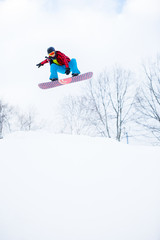 Image of sporty man in helmet with snowboard jumping in snowy resort