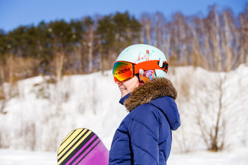 Portrait of sporty woman wearing helmet with snowboard
