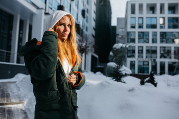 Picture of blonde woman in hood and jacket against winter day