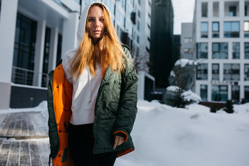 Portrait of blonde woman in hood and jacket against winter day