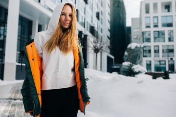 Image of blonde girl in hood and in jacket against winter day