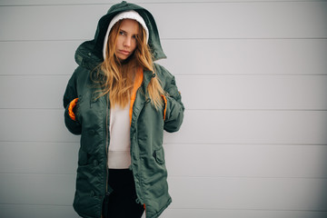 Picture of blond model in hood and in jacket against gray wall