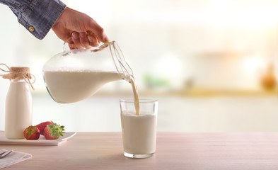 Serving breakfast milk with a jug in a glass on a white wooden kitchen table