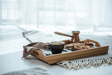 Cup with coffee, turk and cookie on wooden serving tray. Still life details in home interior of living room.