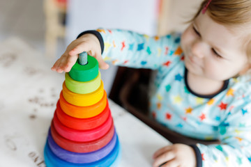 Adorable cute beautiful little baby girl playing with educational wooden rainbow toy pyramid