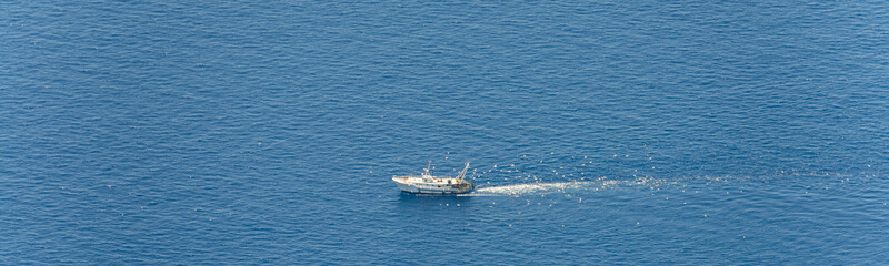 Aerial image of white fishing boat on the Tyrrhenian Sea between Italy and Corsica followed by gulls