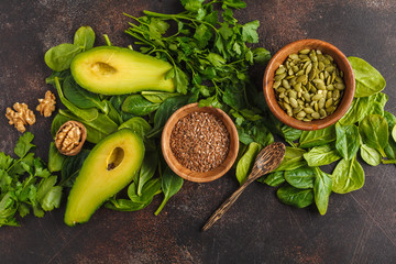 Green salad. Vegan ingredients: spinach, avocado, flax and pumpkin seed. Food background. Detox vegan healthy food concept. Top view, copy space.