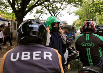 A passenger of Grab bike fixes her helmet next to Uber driver at Manggarai train station in Jakarta