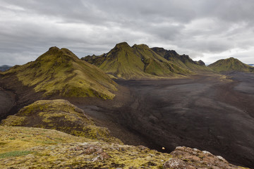 Melancholic Iceland scenery with endless black lava desert and green mountains covered with thick icelandic moss.