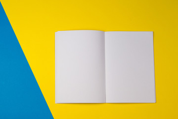 Open blank paper notebook on yellow, and blue color background.
