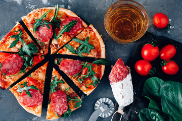 Pizza with ingredients on a black background, salami, spinach, tomatoes and beer.