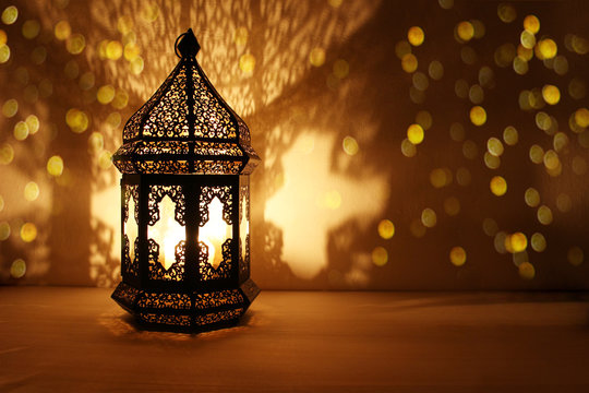 Ornamental Arabic lantern with burning candle glowing at night and glittering golden bokeh lights. Festive greeting card, invitation for Muslim holy month Ramadan Kareem. Dark background.